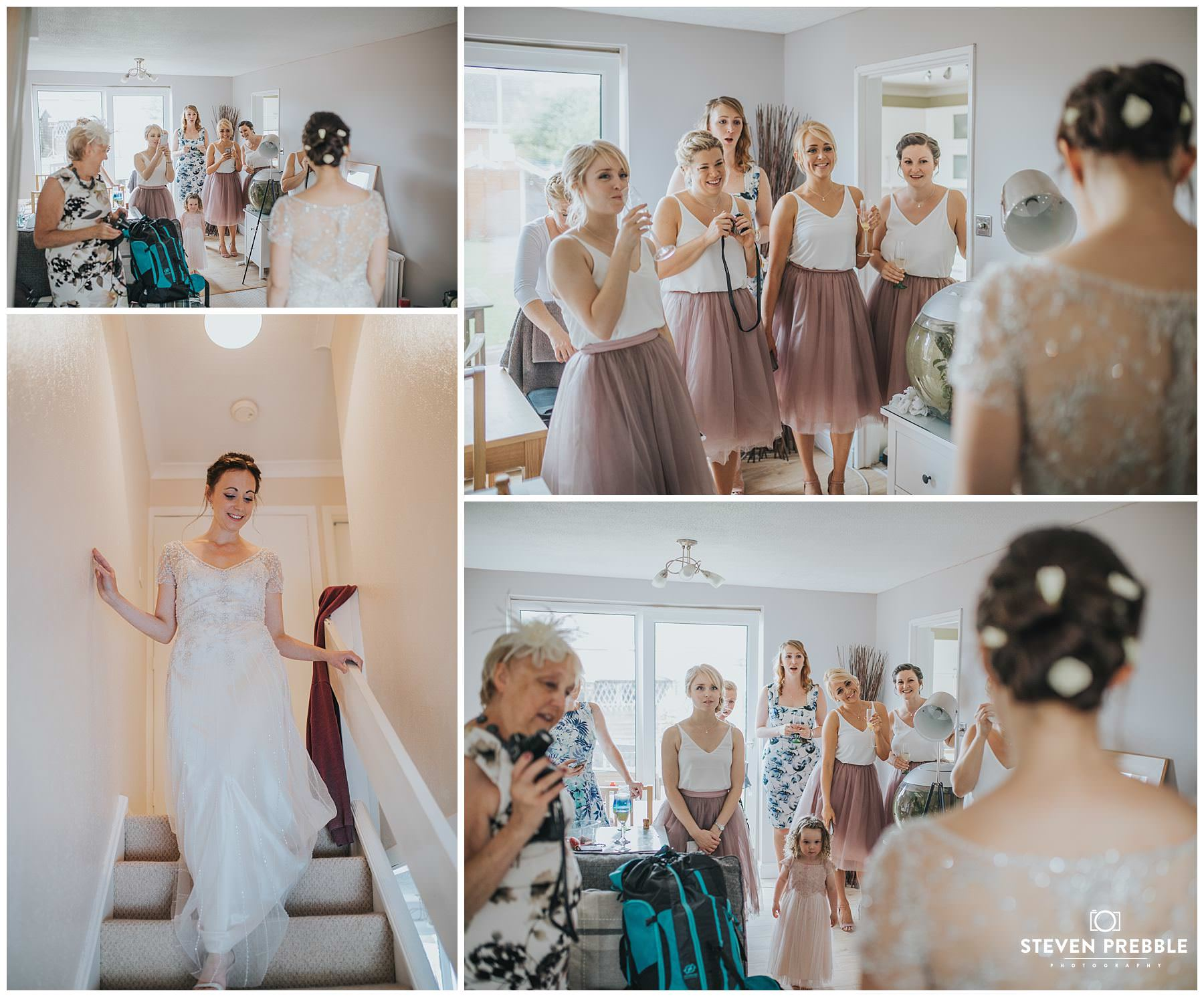 Bride revealing dress to bridesmaids