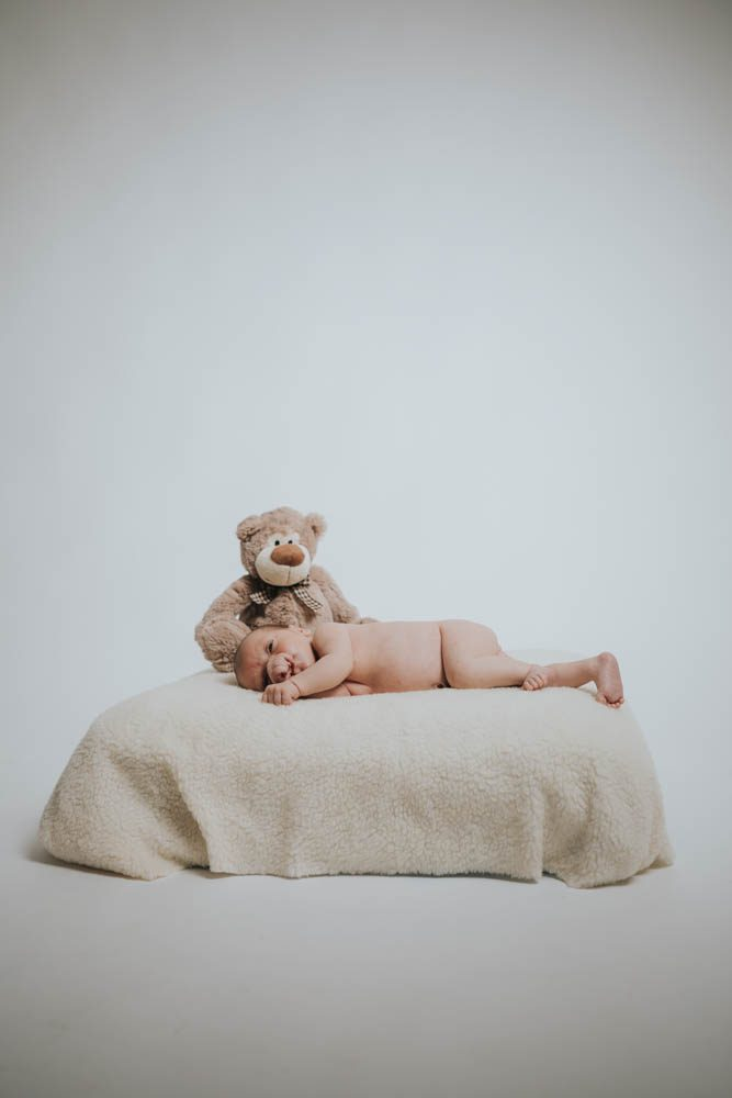 newborn photoshoot cornwall baby sleeping on cushion with teddy bear