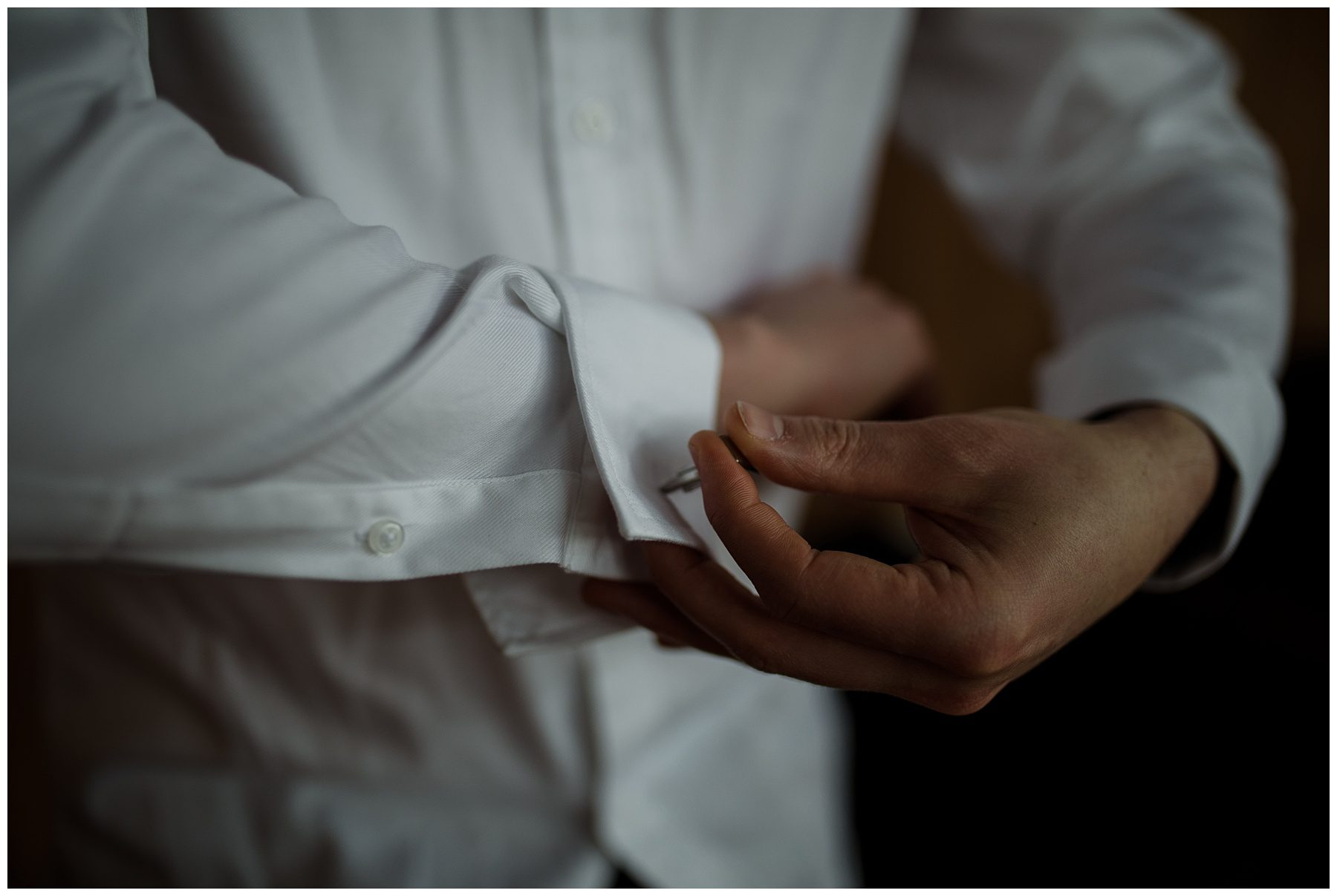 Groom putting on cufflink