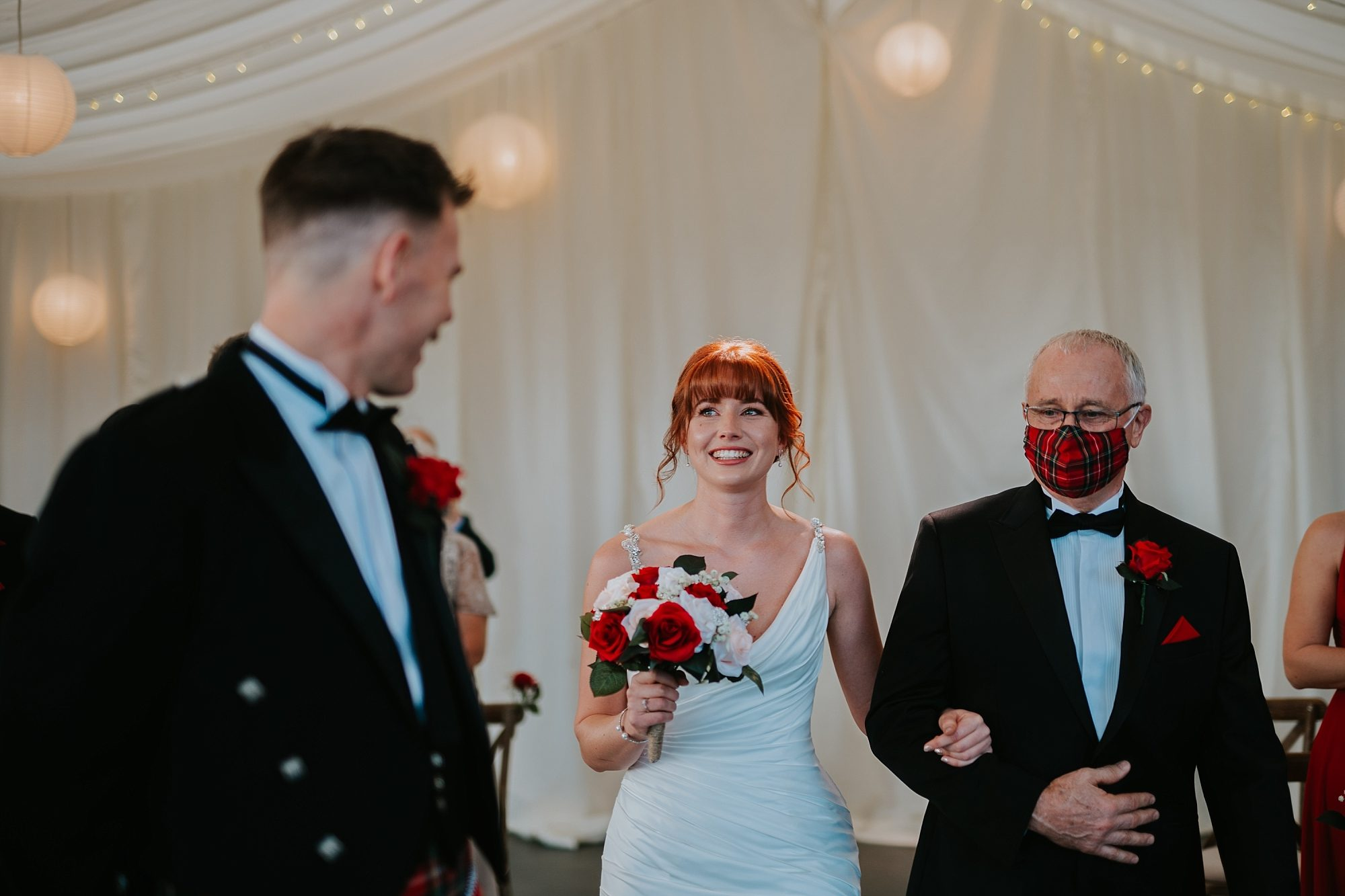 father of bride walking down aisle with face mask
